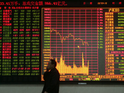 A Chinese shareholder walks by a big screen showing share prices