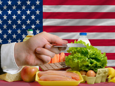 Man stretching out credit card to buy food in front of complete wavy national flag of usa