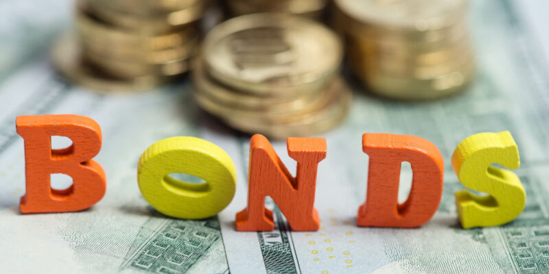 Bonds investment at wooden letters on US Dollar bills and golden coins