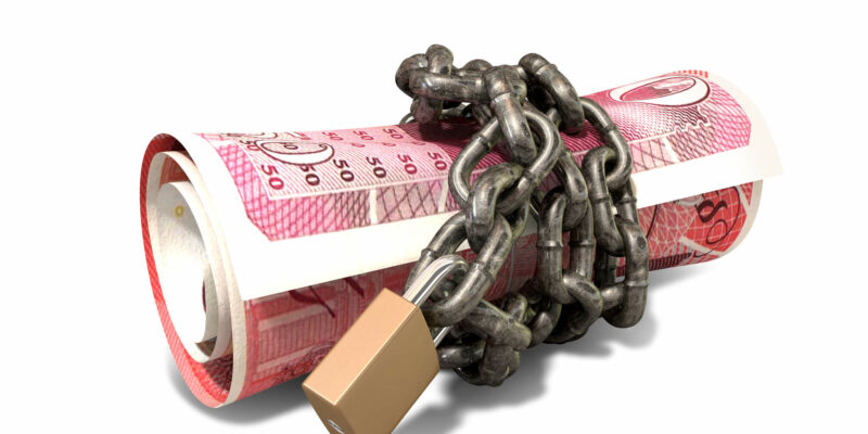 A rolled up british one hundred pound note wrapped with chains and secured with a padlock