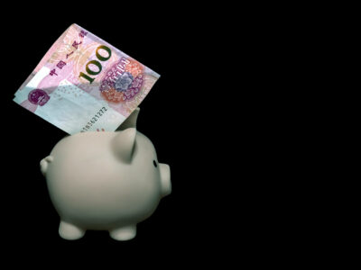 A piggy bank with a 100 yuan bill inside on a black background.