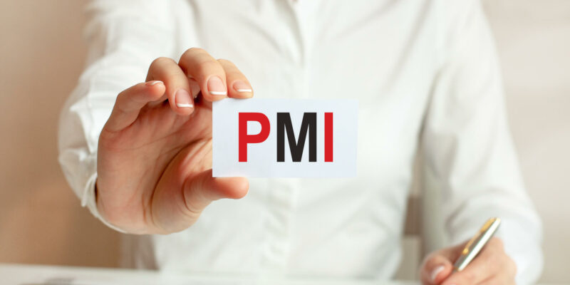 A woman in a white shirt holds a piece of paper with the text: PMI.