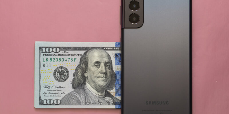 Phantom Grey and 100 dollar banknote on pink background
