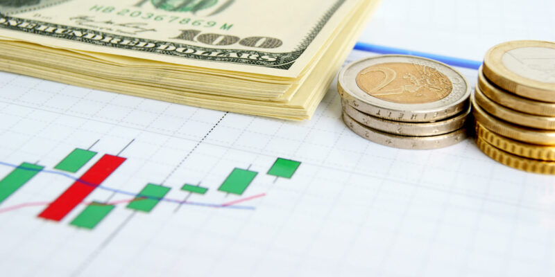 Dollar notes and euro coins on the exchange chart background