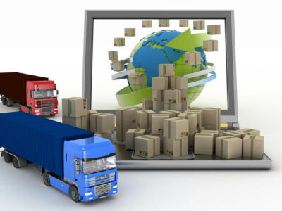 Cardboard boxes around the globe on a laptop screen and two trucks.