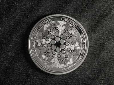 Cardano coin with logo in black and white with dark background.