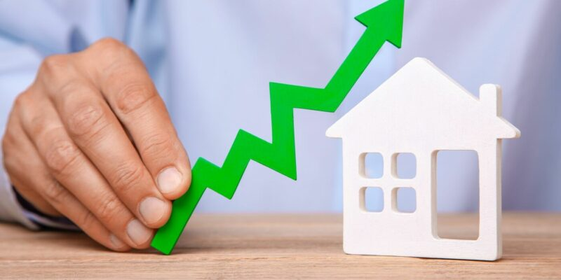 Rising house prices. Man is holding green arrow up in his hand and house on the table.