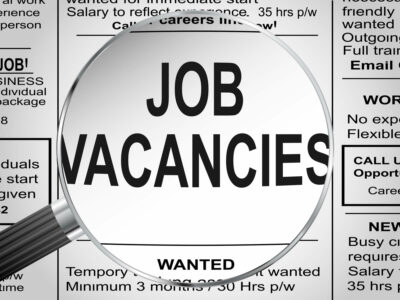 Newspaper clipping. Jobs vacancies under magnifying glass