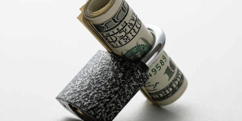 Roll of dollar bills threaded through a padlock shank resting at an angle on a white background in a financial security concept