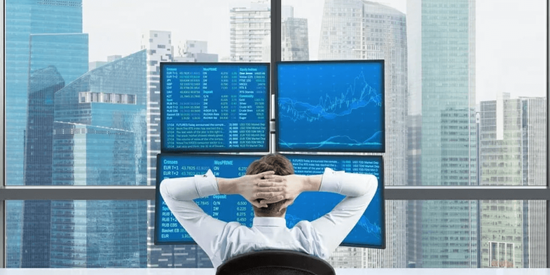 resting businessman in front of 4 screens
