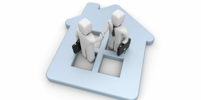 Two people shake hands on the background of the house.Successful real estate deal