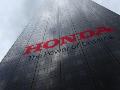 Honda logo on a skyscraper facade reflecting clouds. Editorial 3D