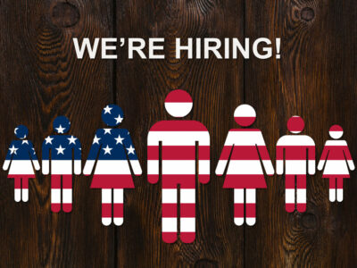 Paper men colorized into the color of the usa flag on wooden background with text WE'RE HIRING. Business concept.